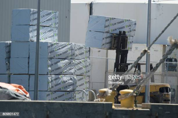 A fork lift stacks bundles of lumber as they are unloaded from a bulk carrier ship at Port Canaveral in Cape Canaveral Florida US on Wednesday July 5...
