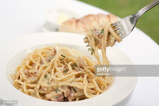 A fork spindles from a bowl of linguine carbonara