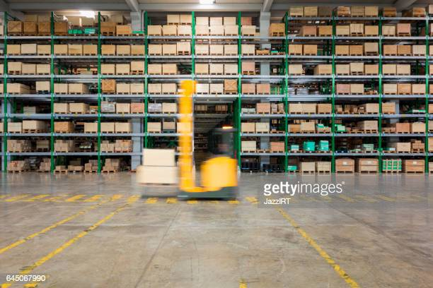 Forklift carrying cardboard box in warehouse