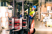 forklift driver in protective vest driving forklift at warehouse of freight forwarding company