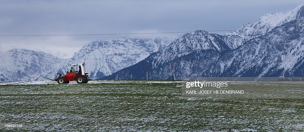 A forklift drives on a snow covered field near Enisried, southern Germany, on January 3, 2013. Meteorologists forecast rainy weather with temperatures around six degrees for southern Germany.