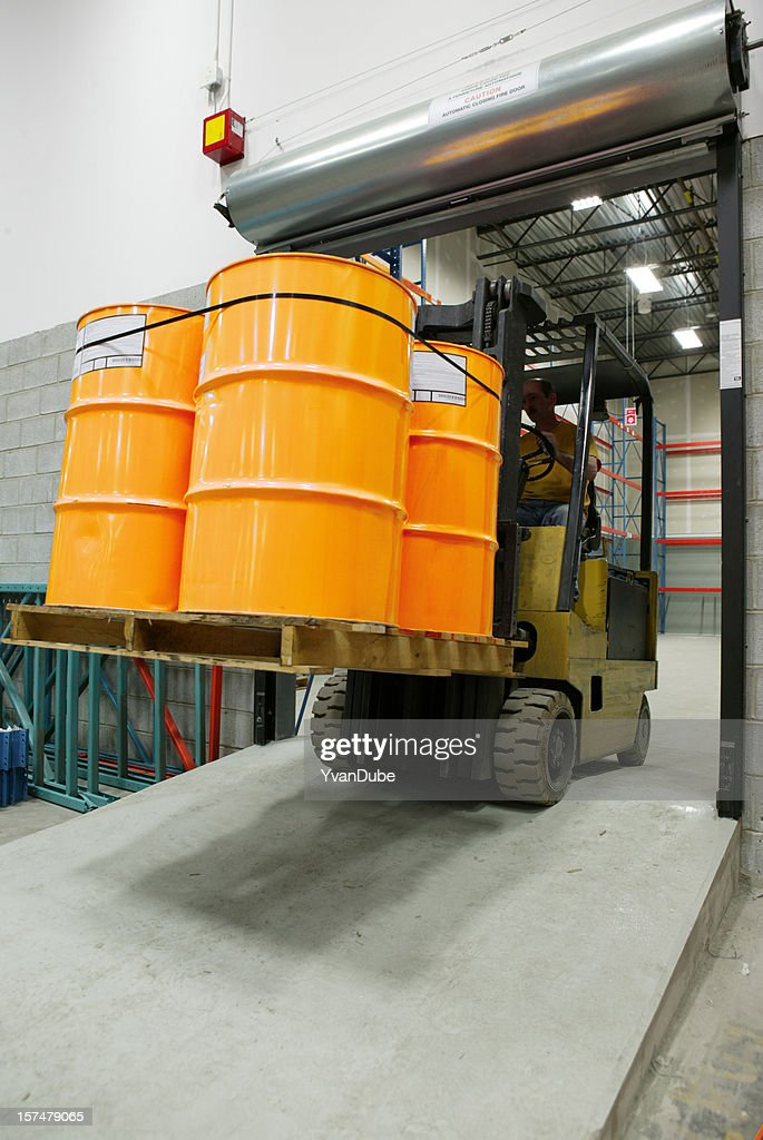 forklift in warehouse carrying yellow barrel : Stock Photo