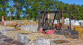 Forklift loading and moving material down from a truck.