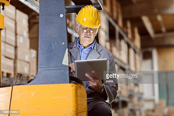 forklift operator at warehouse use digital tablet  for reviewing  inventory