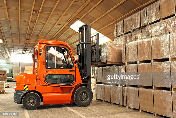 Forklift operator loading boxes in warehouse