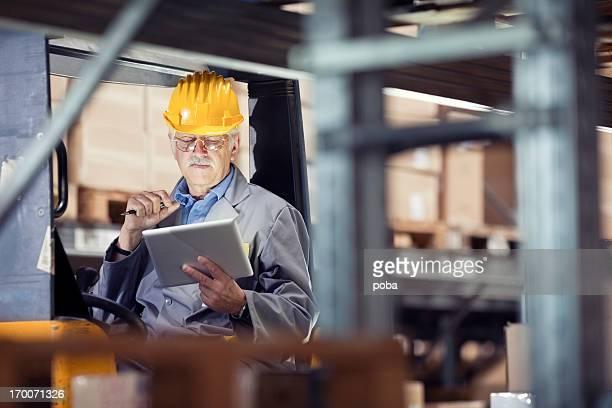 Opérateur de chariot élévateur à la recherche à une tablette numérique