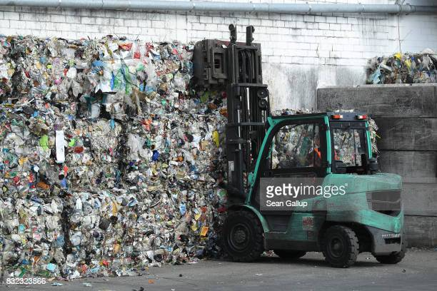 A forklift stacks bales of sorted materials at the ALBA sorting center for the recycling of packaging materials on August 15 2017 in Berlin Germany...