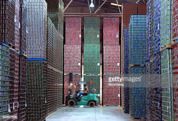 A forklift truck passes through an aisle of stacked aluminum beverage cans ready for distribution at an Amcor Ltd beverage can production facility in...