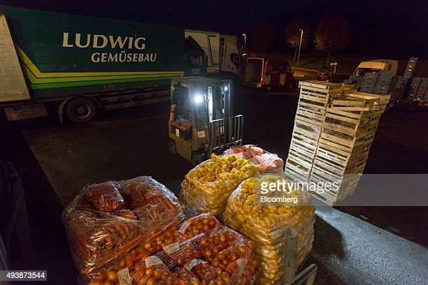 A forklift truck transports pallets of carrots and potatoes to a cargo truck outside the wholesale food market in Frankfurt Germany on Friday Oct 23...