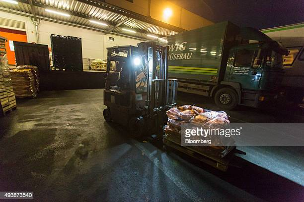 A forklift truck transports pallets of carrots outside the wholesale food market in Frankfurt Germany on Friday Oct 23 2015 Falling prices and...