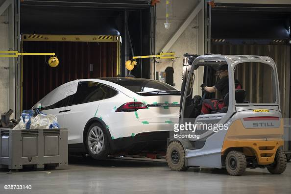 A forklift truck unloads a Tesla Model X sports utility vehicle from a shipping container as it arrives for assembly for the European market at the...