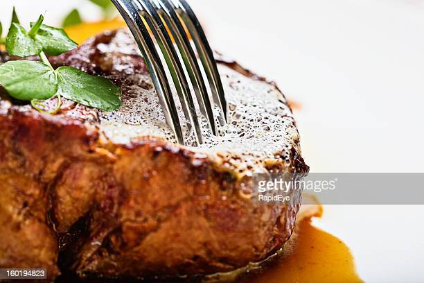 Fork-tender: fork gently prods juicy grilled steak, testing for tenderness