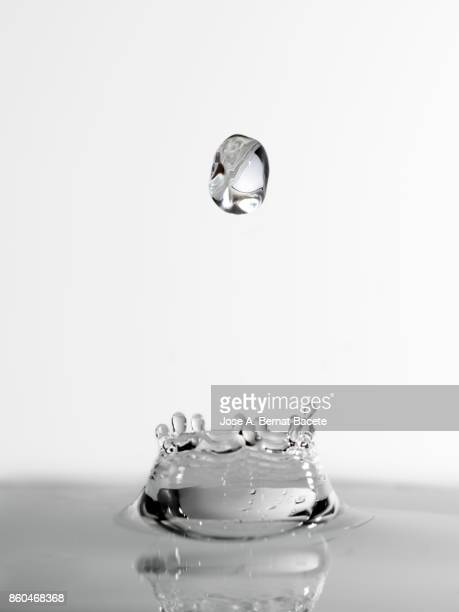 Form or figure of a water drop splashing on a water surface with a white bottom