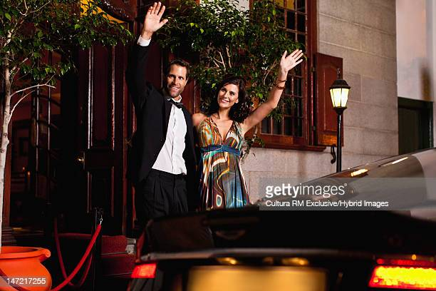 Formal couple waving down taxi