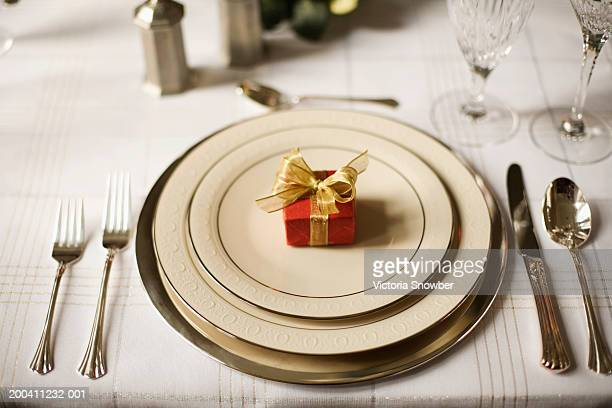 Formal dinner setting with wrapped present