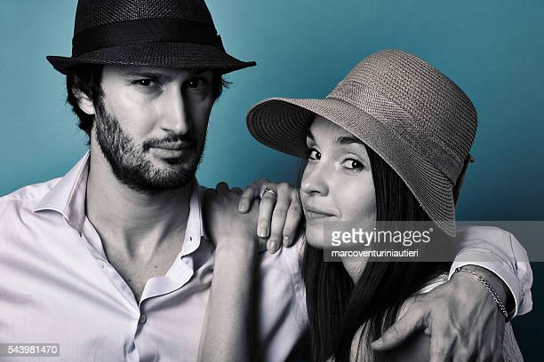Formal portrait of cool young couple wearing hats