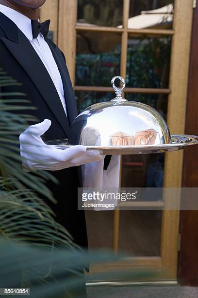 Formal server holding silver tray