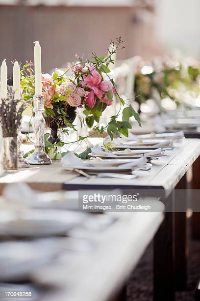 A formal wedding breakfast table, laid for a feast. Fresh flowers in the centre.