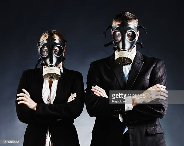 Formally dressed couple in gas masks fold arms and stare