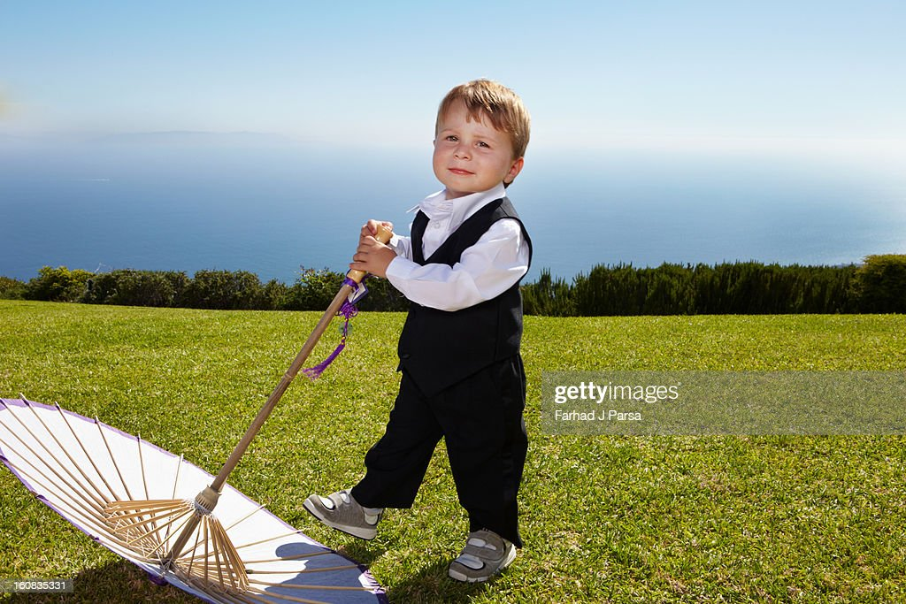 Formally dressed two year old boy poses outside. : Stock Photo