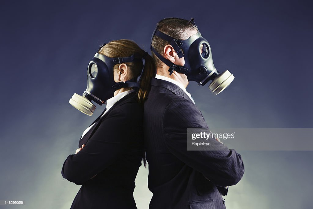 Formally-dressed couple in gas masks stand backs to each other : Stock Photo