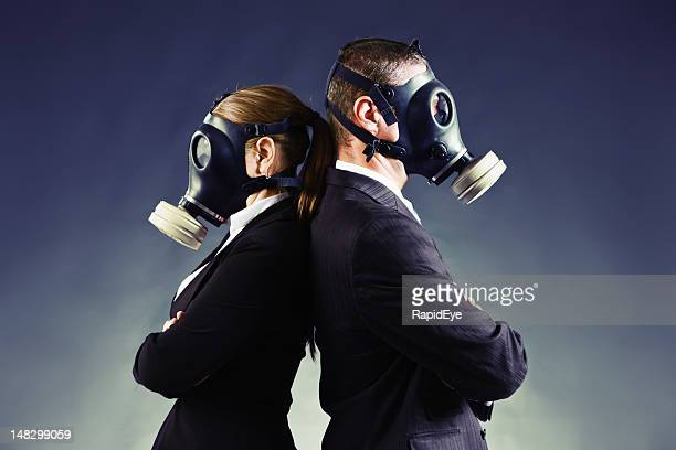 Formally-dressed couple in gas masks stand backs to each other