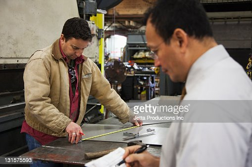 Forman and worker working in factory : Stock Photo