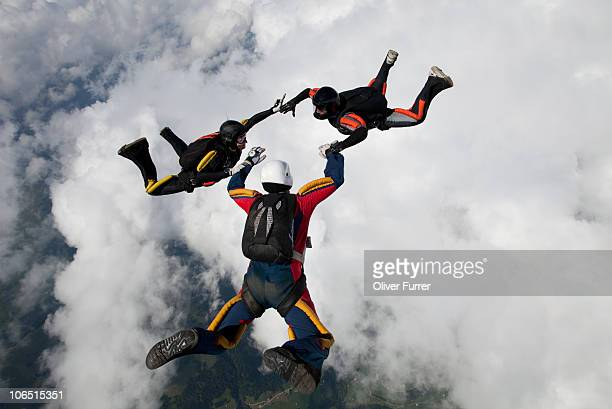Formation skydivers holding hands over clouds.