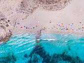 Aerial overhead view of large amount of yachts anchored off the coast of Formentera Ibiza, with turquoise Mediterranean Sea and ocean blue water.