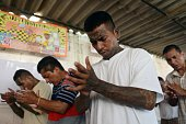 Former MS13 gang members pray at the Apanteos prison in Santa Ana 66 km west of San Salvador on July 15 2016 Apanteos is a model prison in the...