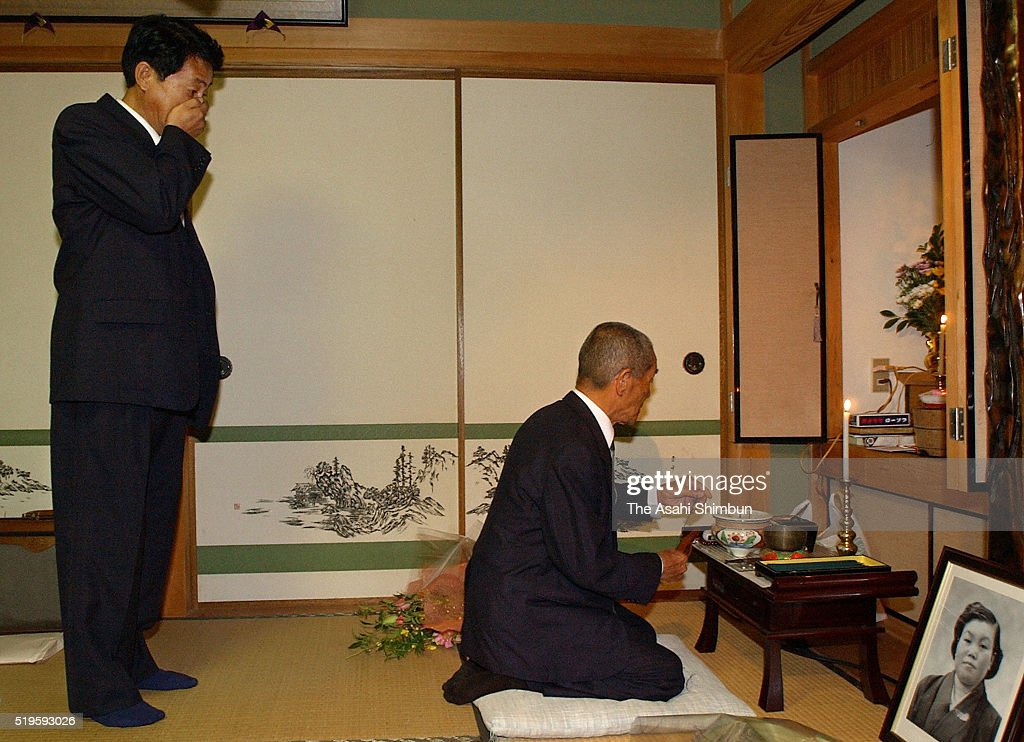 Former abductee by North Korea Yasushi Chimura and his father Tamotsu pray for late mother at his home on October 17 2002 in Obama Fukui Japan