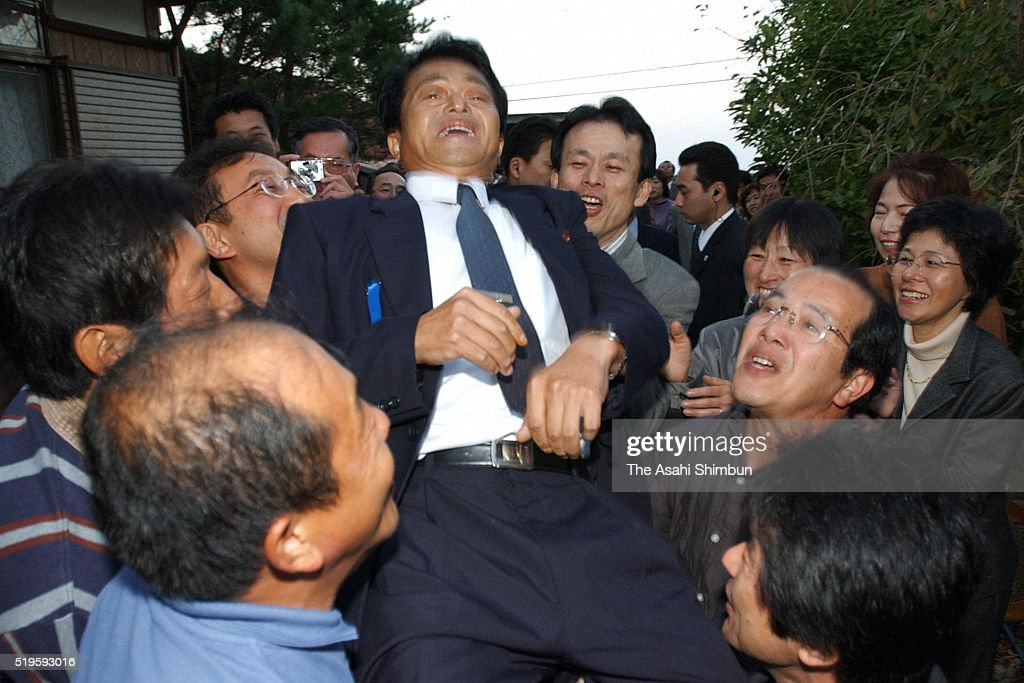 Former abductee by North Korea Yasushi Chimura is thrown into the air on arrival at his home on October 17 2002 in Obama Fukui Japan