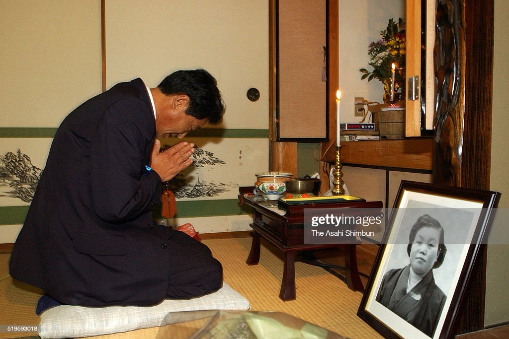 Former abductee by North Korea Yasushi Chimura prays for her late mother at his home on October 17 2002 in Obama Fukui Japan
