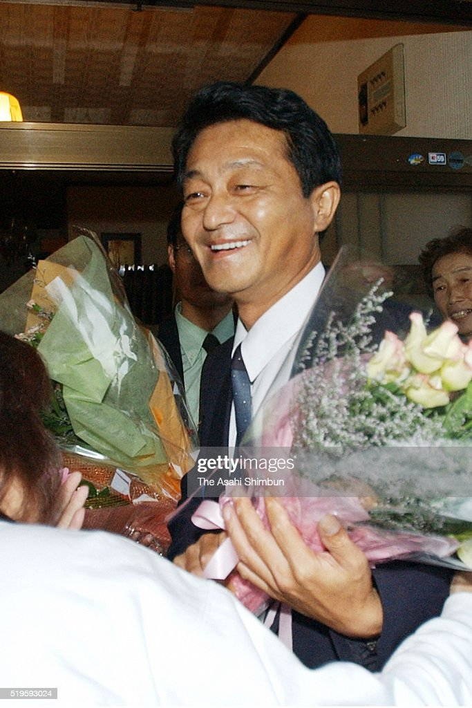 Former abductee by North Korea Yasushi Chimura receives flower bunches on arrival at his home on October 17 2002 in Obama Fukui Japan