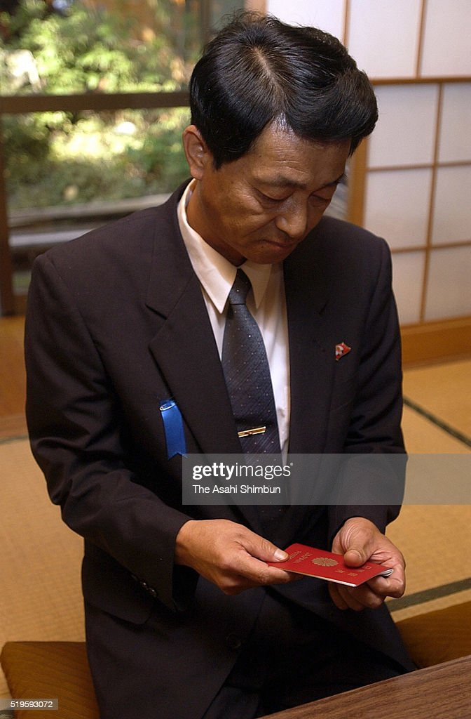 Former abductee by North Korea Yasushi Chimura receives his passport at his home on October 18 2002 in Obama Fukui Japan