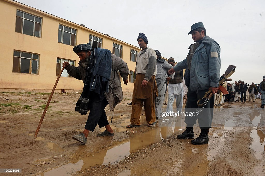 Former Afghan drug addicts walk down a dirt road after receiving two moths treatment at an Afghanistan Ministry of Counter Narcotics centre in Herat on January 28, 2013. Afghan police and health officials collected 350 addicts from the streets of Herat and forced them to stay in a centre to receive treatment for two months. 130 were released after they stopped using and were ready to go back to society, police and health officials said. AFP PHOTO/ Aref Karimi