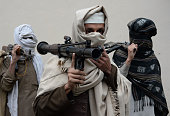 Former Afghan Taliban fighters carry their weapons before handing them over as part of a government peace and reconciliation process at a ceremony in...