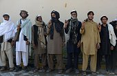 Former Afghan Taliban fighters hold weapons as they wait to hand them over as part of a government peace and reconciliation process at a ceremony in...