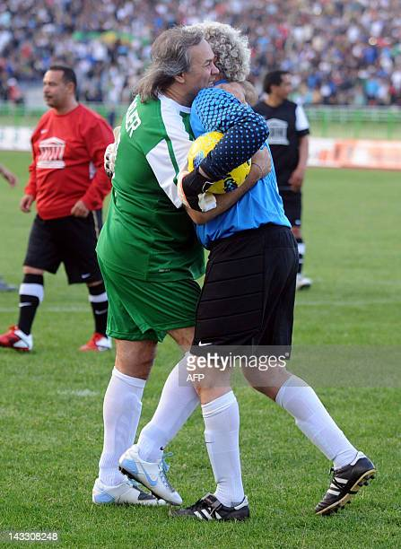 Former Algerian football star and UNESCO Goodwill Ambassador Rabah Madjer embraces former Belgian goalkeeper JeanMarie Pfaff as they take part in a...