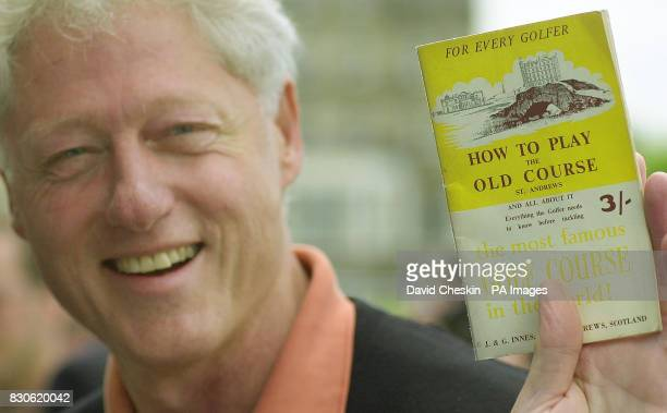 Former American President Bill Clinton holds up his 50 yearold guide book as he arrives at the Old Course at the Royal and Ancient Golf Club in St...