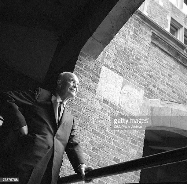 Former American President Dwight D Eisenhower stands under an archway and glances upwards during the filming of a CBS News Special entitled 'Young Mr...