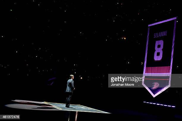 Former Anaheim Ducks player Teemu Selänne watches as his jersey is raised during his retirement ceremony prior to the NHL game between the Winnepeg...