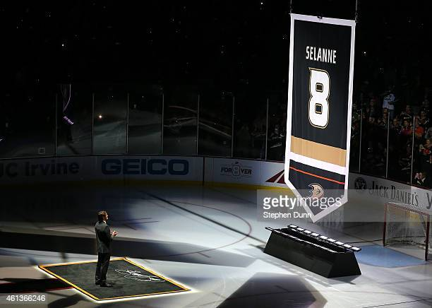 Former Anaheim Ducks star Teemu Selanne stands on the ice as his banner is raised during ceremonies retiring Selanne's number by the Ducks before the...