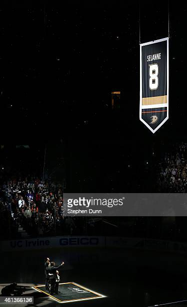 Former Anaheim Ducks star Teemu Selanne stands with his family as his banner is raised during ceremonies retiring Selanne's number by the Ducks...