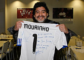 Former Argentina player and manager Diego Maradona shows a team jersey signed by head coach Jose Mourinho of Real Madrid after his visit to a Real...