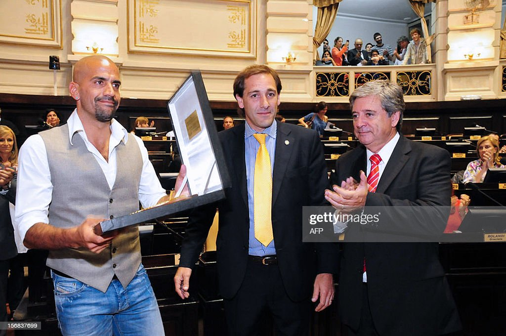Former Argentine football player Juan Sebastian Veron (L) receives a recognition as Outstanding Figure of Sports at the Buenos Aires province's Deputies chamber, chaired by Horacio Gonzalez (R), in Buenos Aires on November 22, 2012.