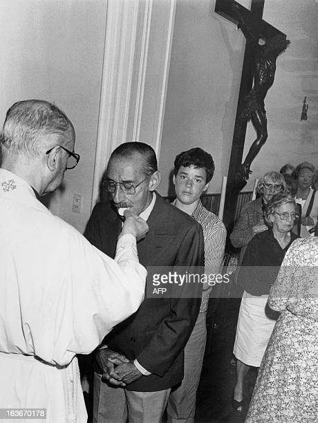 Former Argentine military dictator Gen Jorge Rafael Videla takes communion from a priest of a local church Buenos Aires 30 December 1990 The day...