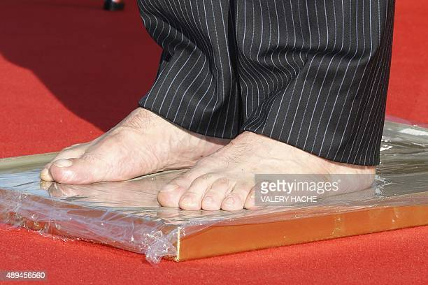 Former Argentinian defender Daniel Passarella makes foot prints during the Foot Print Ceremony as part of the 2015 Golden Foot Award ceremony in...