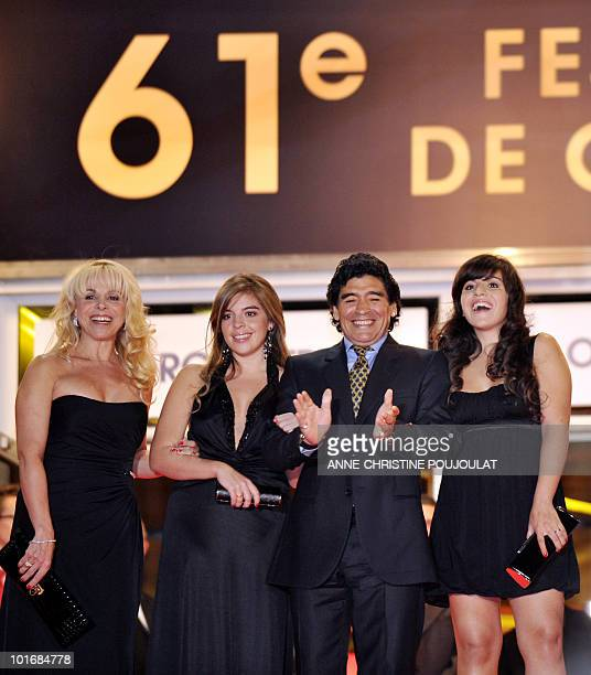 Former Argentinian football player Diego Maradona applauds as he arrives with his wife Claudia and daughters Dalma and Giannina to attend the...