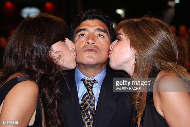 Former Argentinian football player Diego Maradona is kissed bu his daughters Giannina and Dalma as he arrives to attend the screening of Serbian...